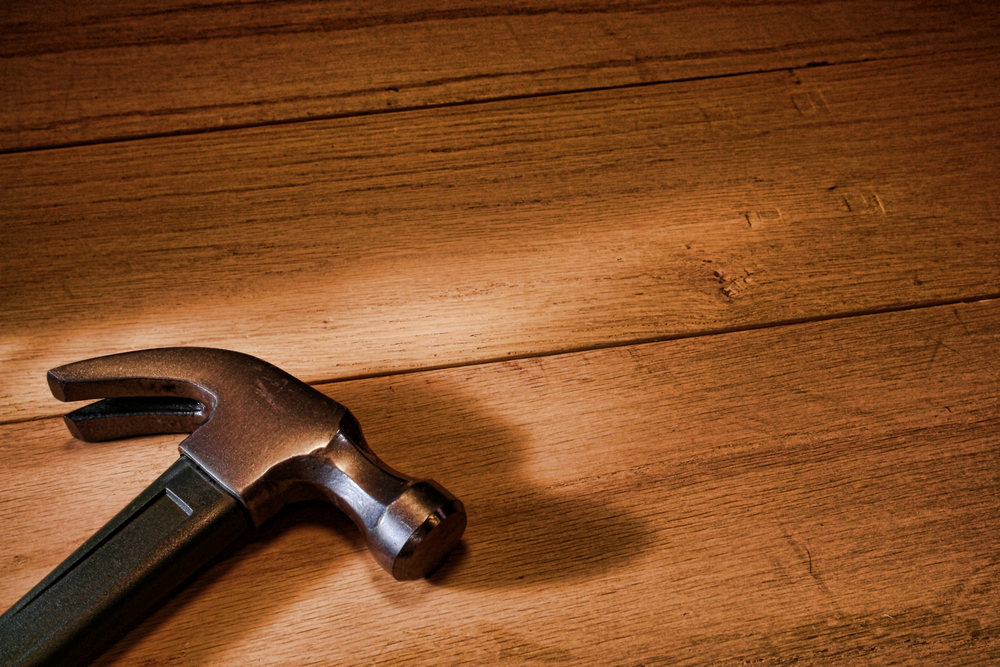 Claw hammer resting on a wood background