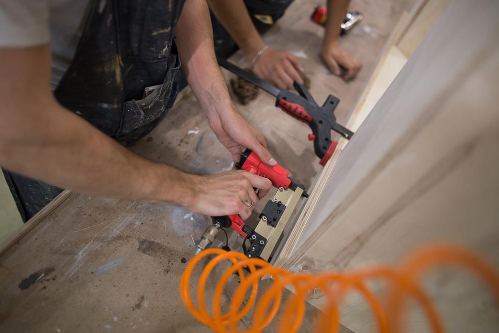 carpenters using pneumatic nail gun