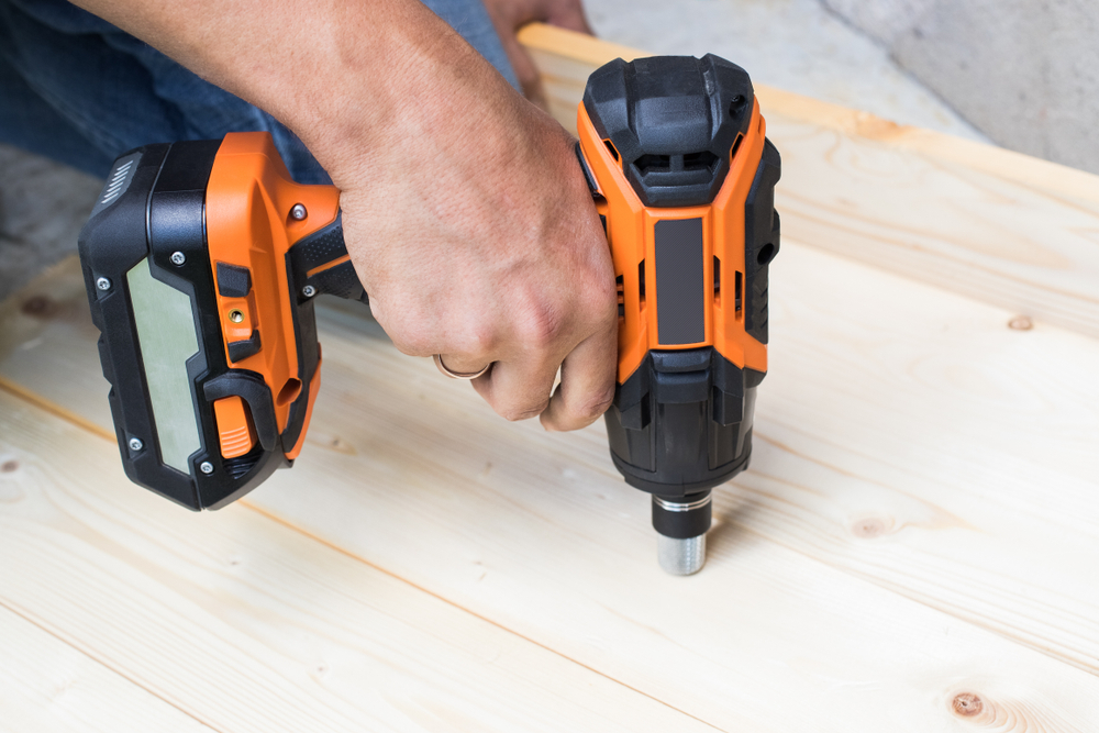 man using impact wrench on wood