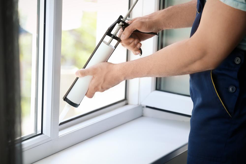 person using caulking gun on window