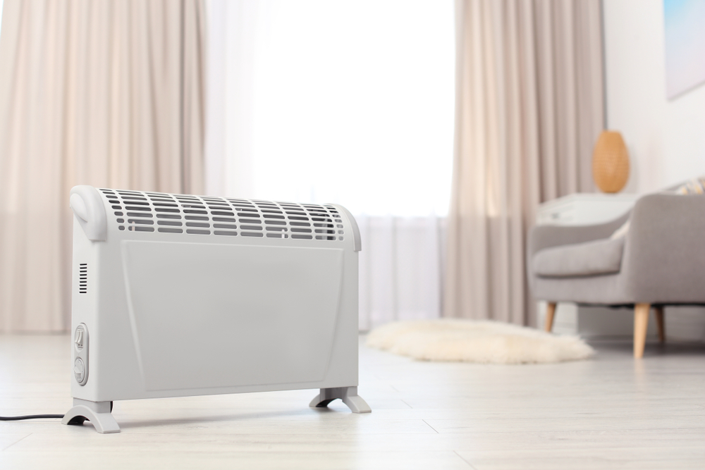 a white electric heater on a wood floor
