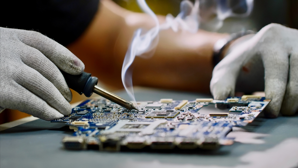 Technician soldering component on circuit board