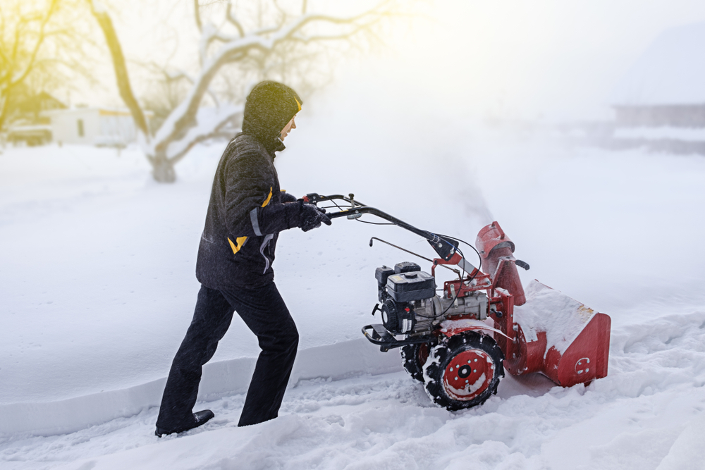 man removes snow with blower