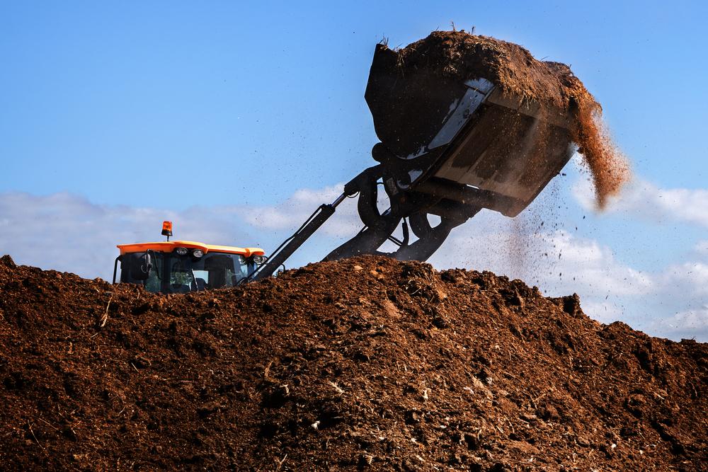 large excavator working on manure heap
