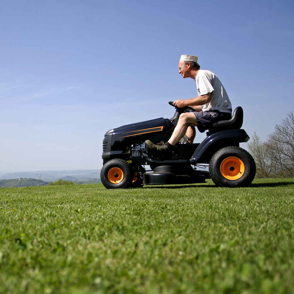 man driving a lawn tractor across a lawn