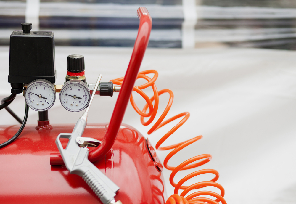 red air compressor with gauges connected to a hose and air tool