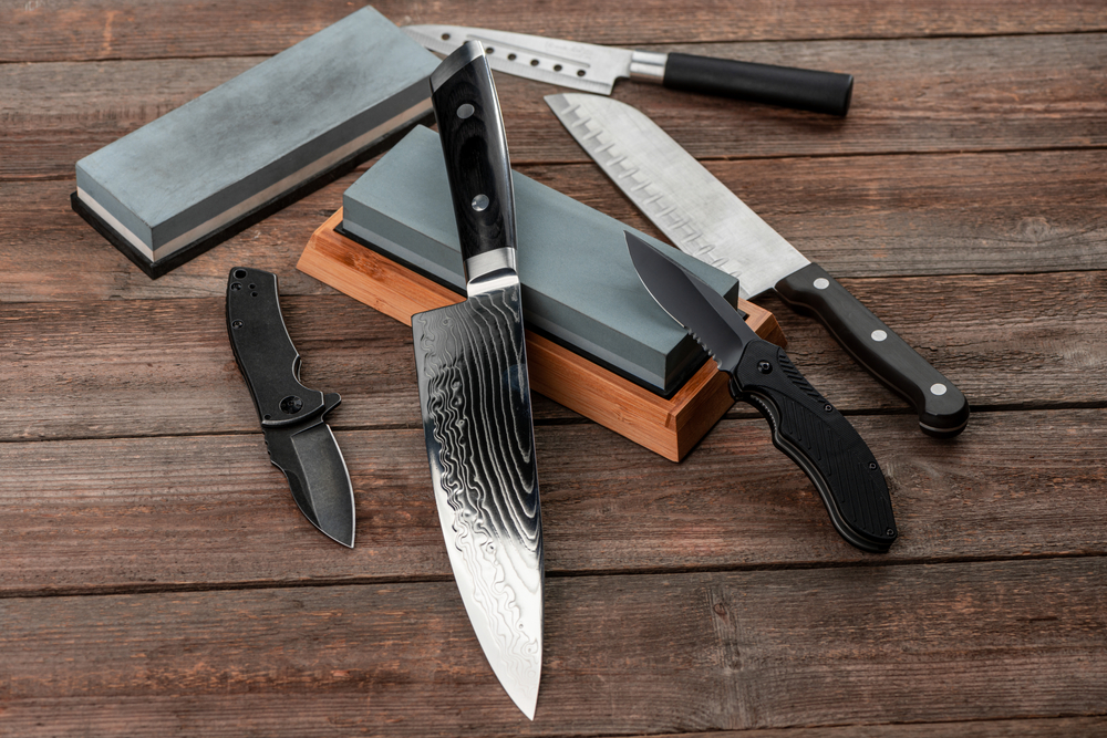 assorted knives sitting on top of whetstone