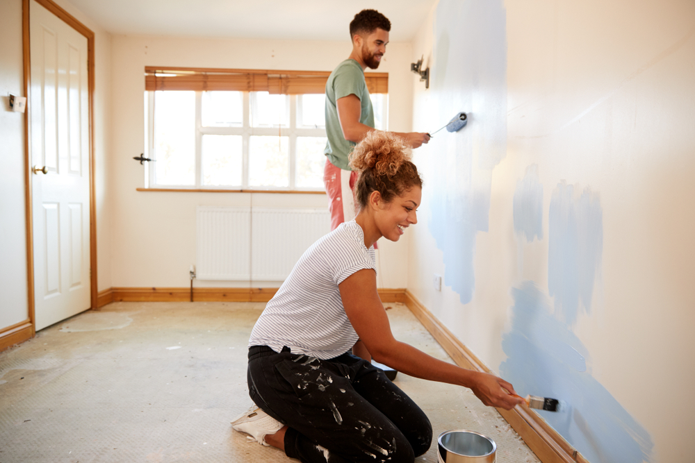 man and woman painting a beige room blue