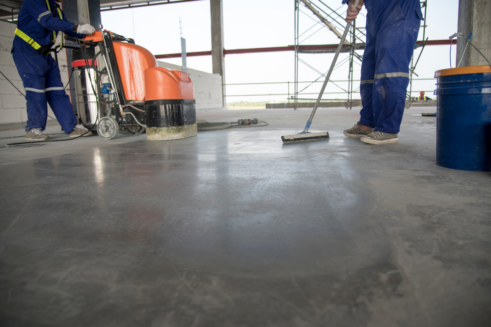 two professional polishing and cleaning a concrete floor