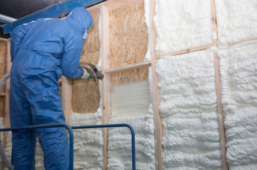 worker installing spray foam insulation