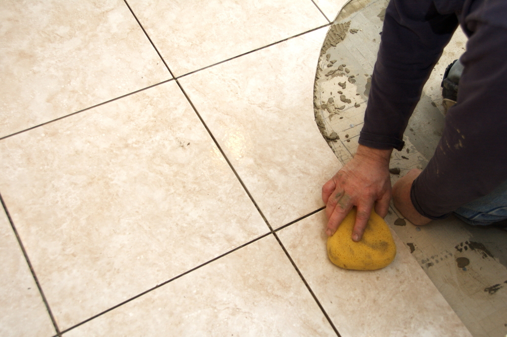 A man installing sanded grout onto large floor tiles