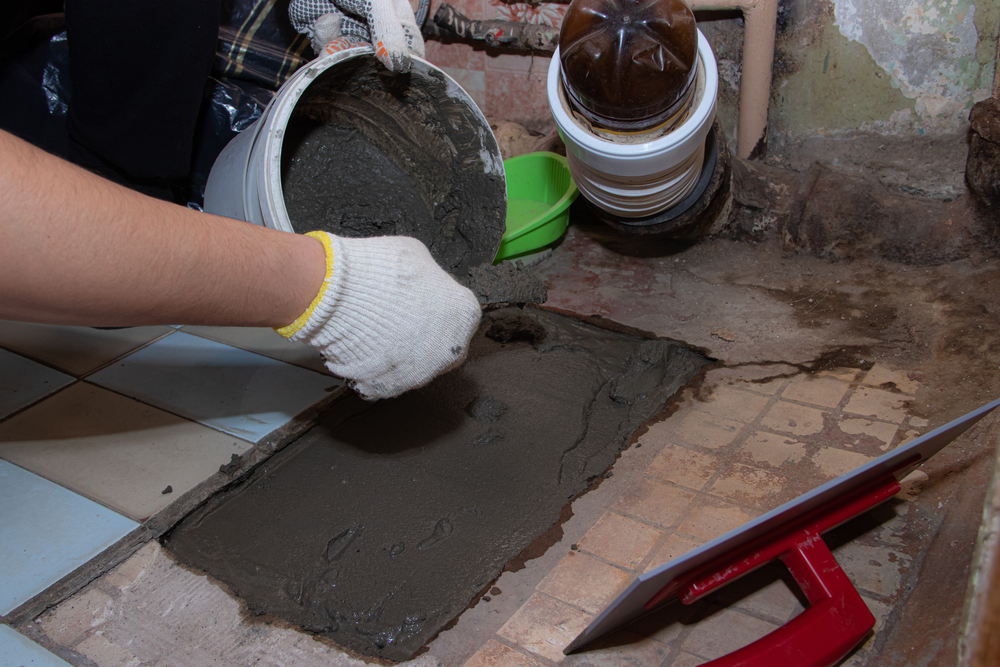 A man using liquid cement to lay down tiles in the bathroom