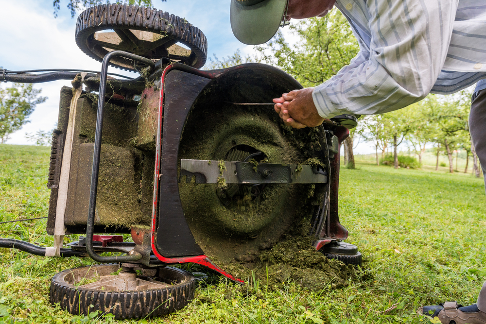 A person cleaning a lawn mower