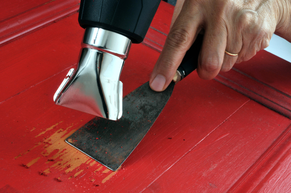 A worker removing paint from wood with a heat gun and spatula
