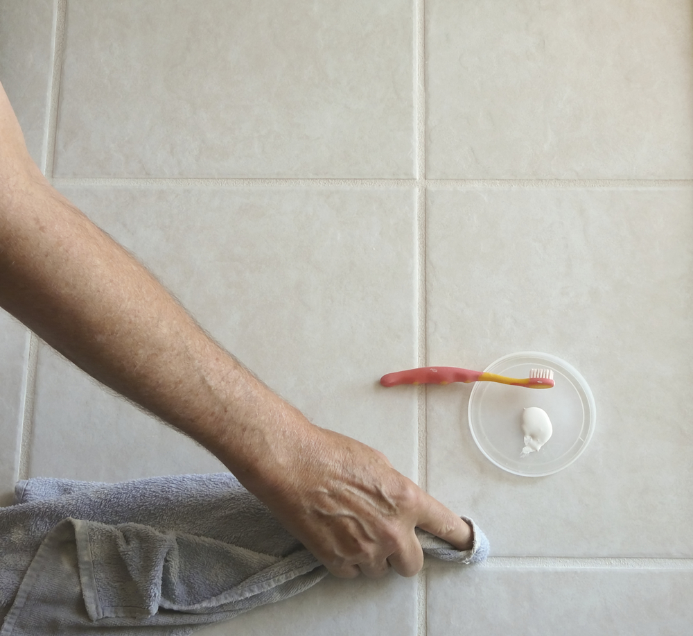 A worker using a toothbrush to clean grout lines