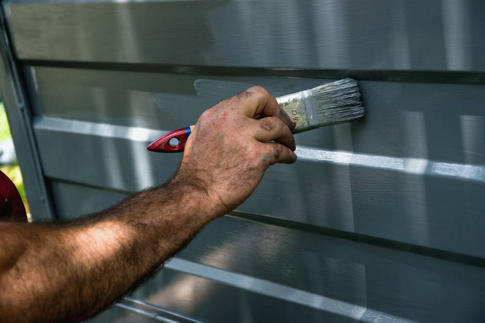 Using a paint brush to paint a garage door