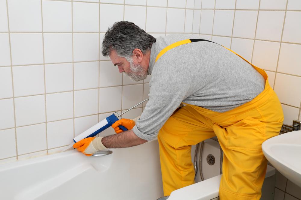 a man caulking a bathtub