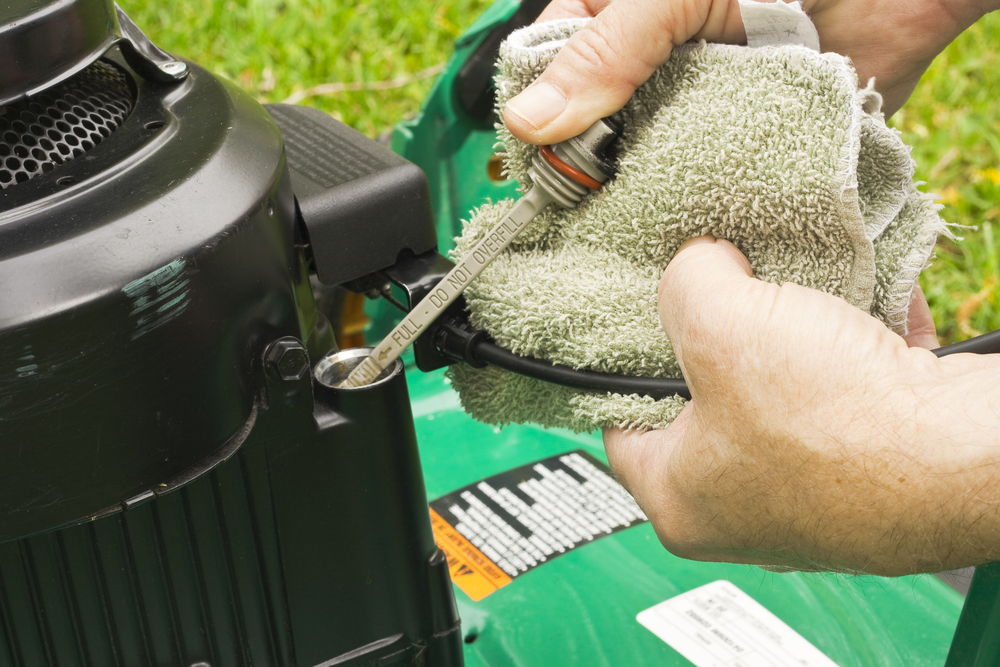 checking the dipstick on a lawn mower