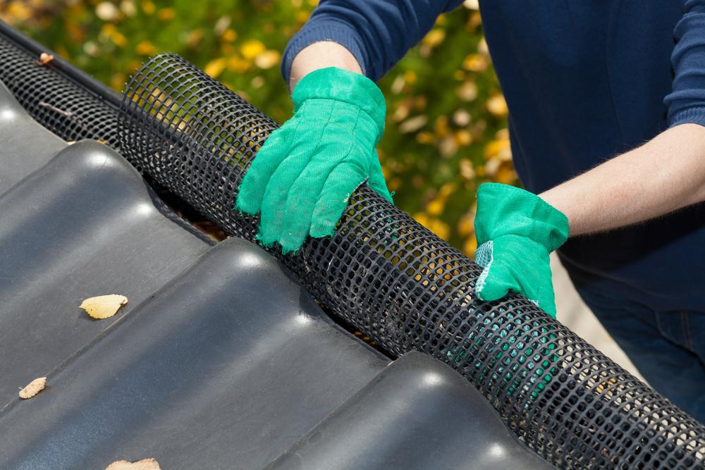 contractor installing leaf guard on rain gutter