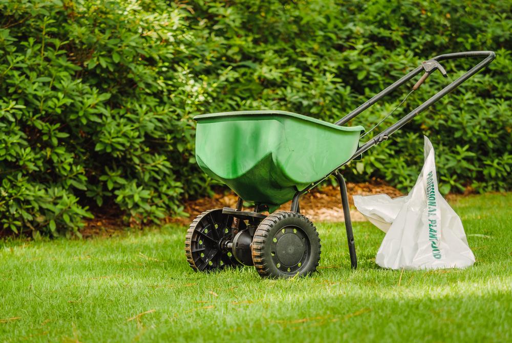 fertilizer spreader resting on lawn with bag of fertilizer