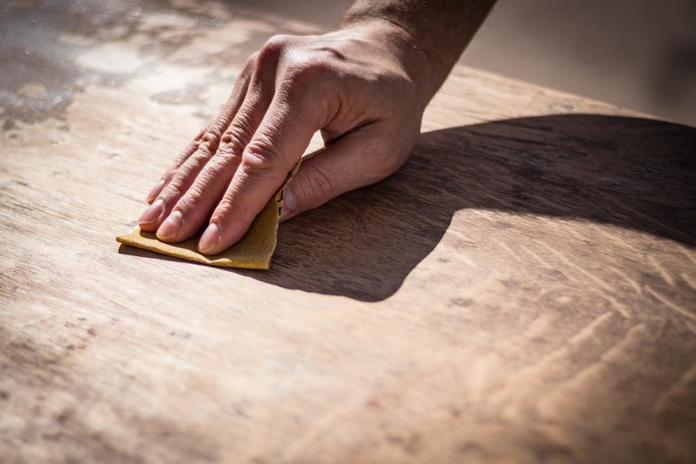 hand sanding a wooden tabletop using sandpaper
