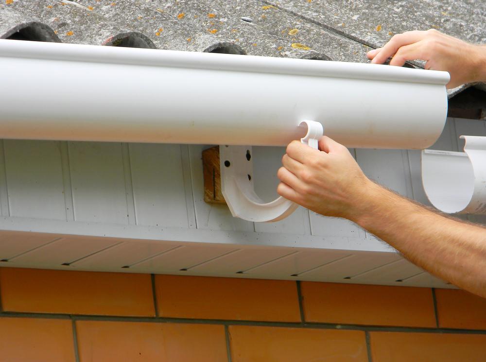 installing a half-round rain gutter on home