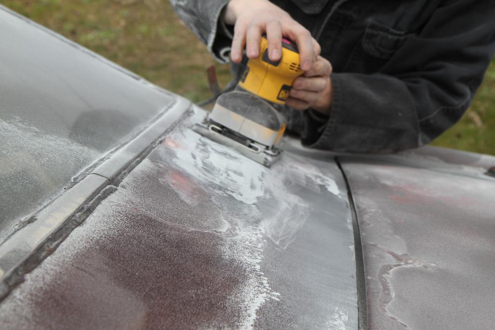 mechanic sanding chrome on car hood