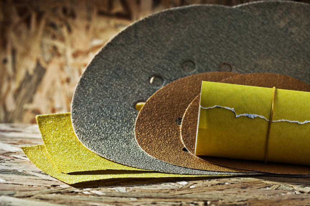rolled sheets of sandpaper on plywood background