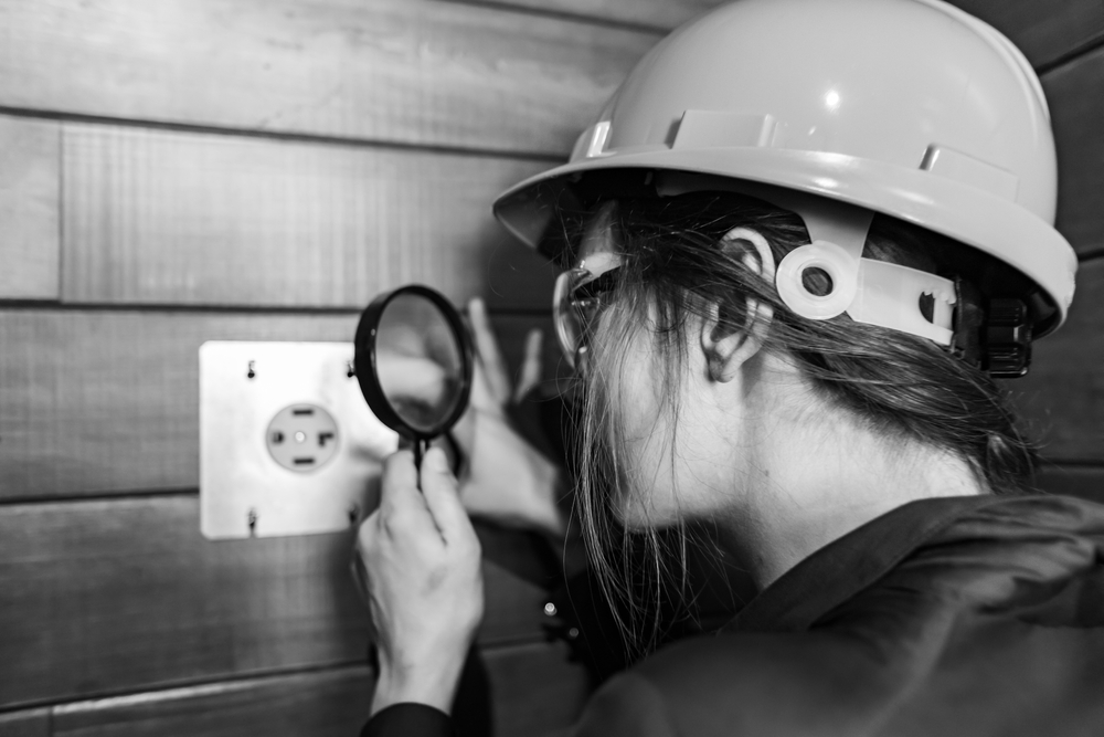woman inspecting 4-prong dryer outlet