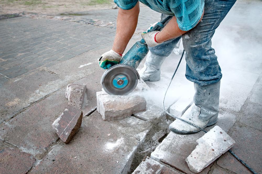 worker using circular saw to cut paver