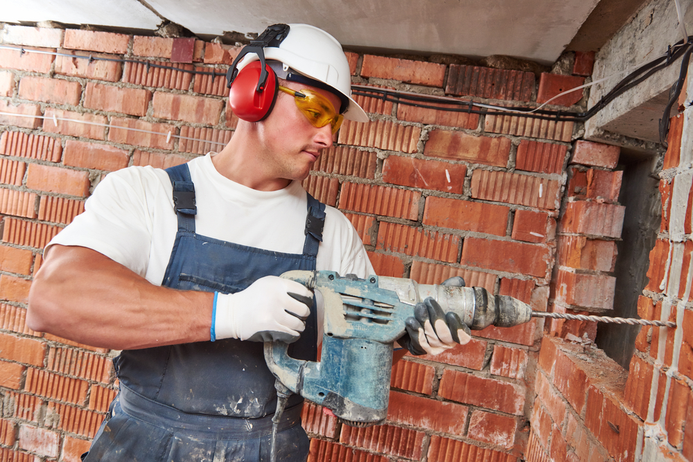 worker using hammer drill on brick