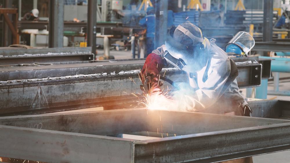 A worker using a flux core welder in a workshop