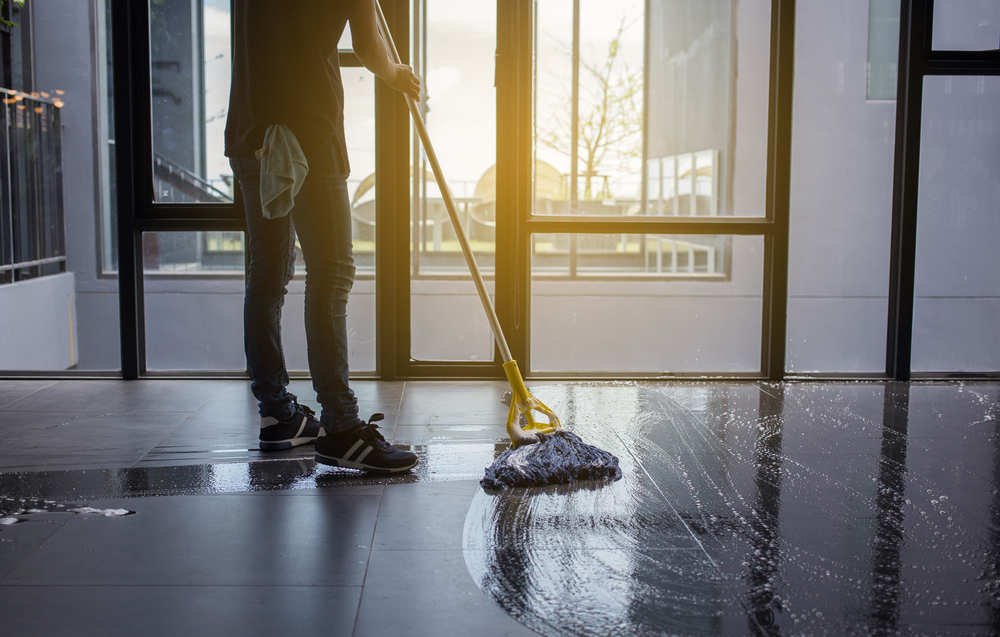 a man mops a tile floor leaving behind a wet figure-eight pattern