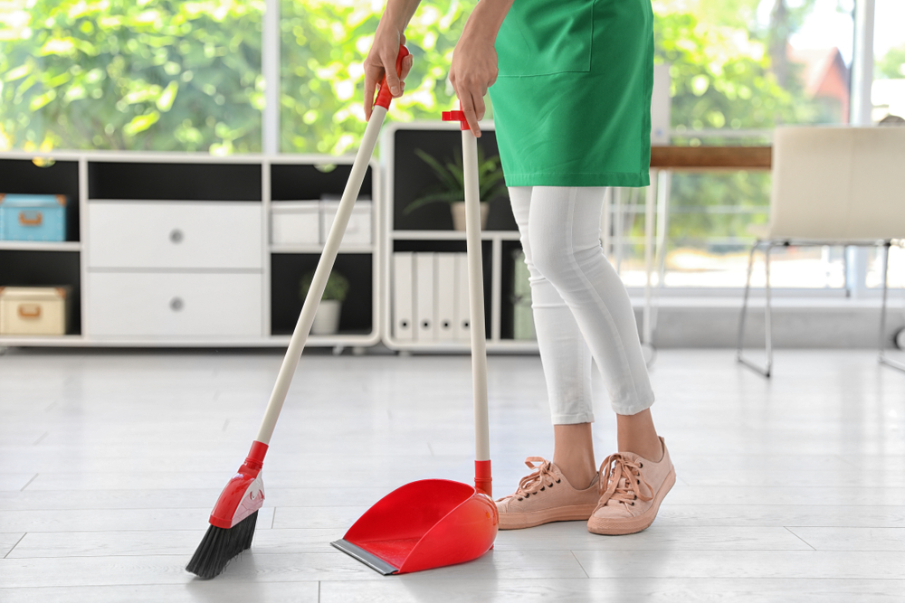a woman wearing a green apron holds a broom and a dustpan