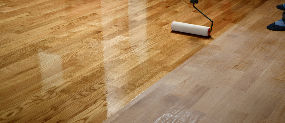 person applying lacquer to a hardwood floor