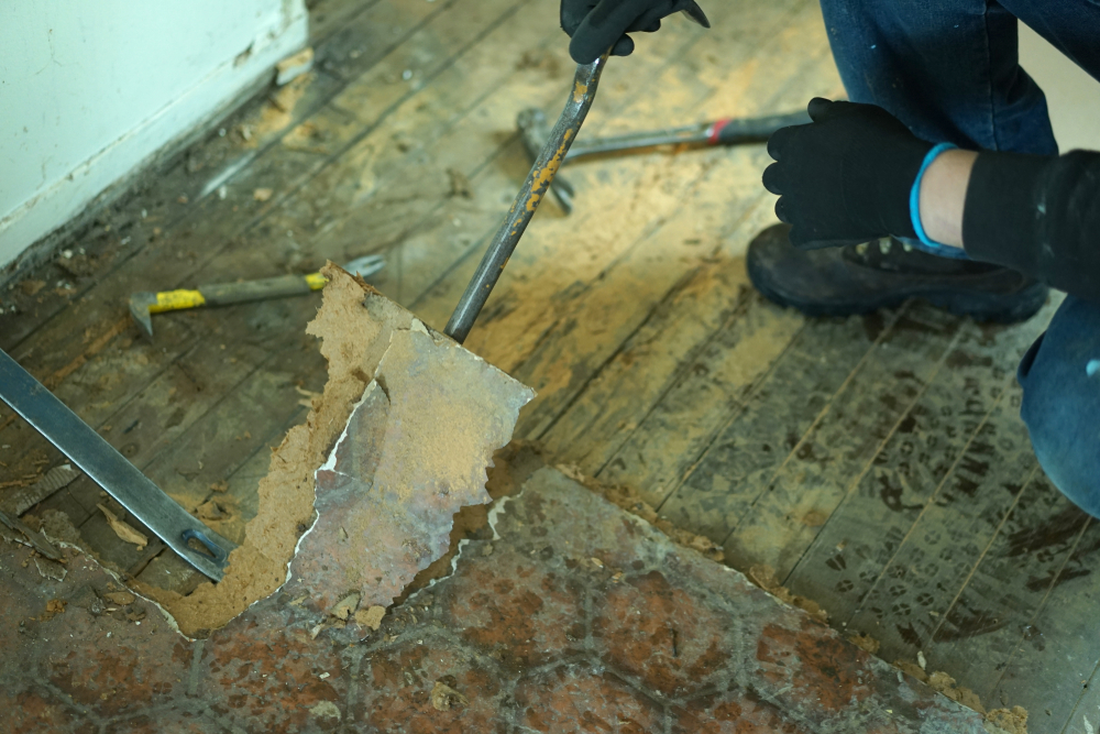 person removing linoleum piece by piece from hardwood subfloor with a crowbar