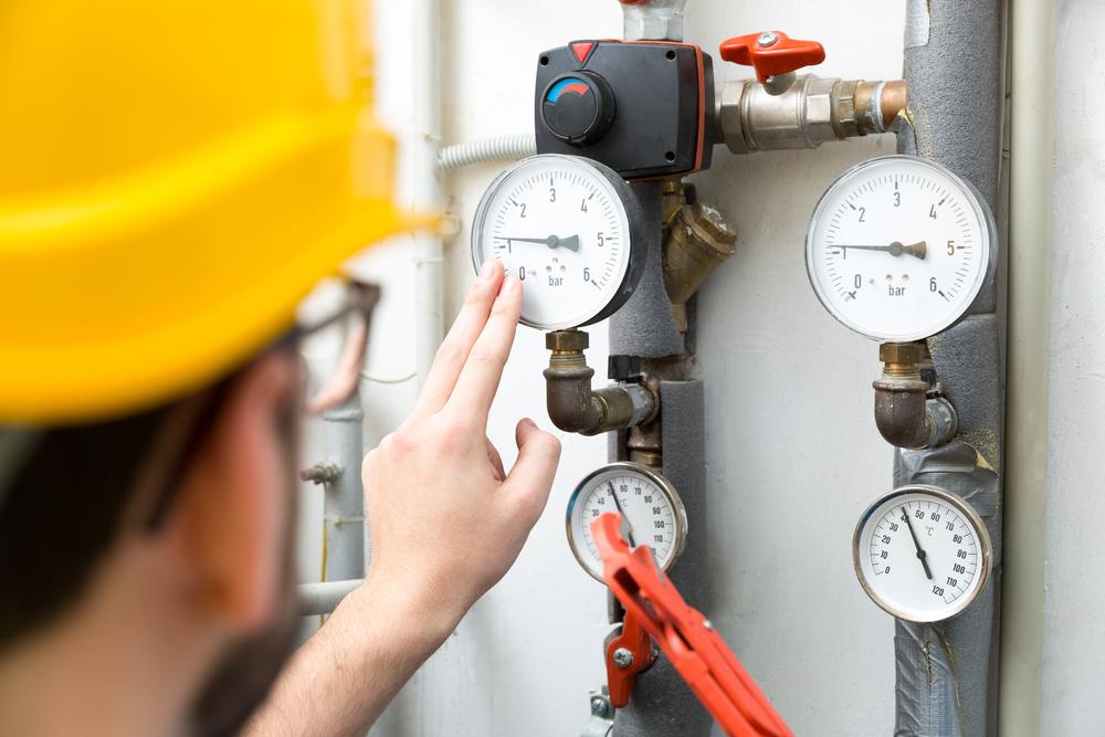 technician tapping pressure gauge