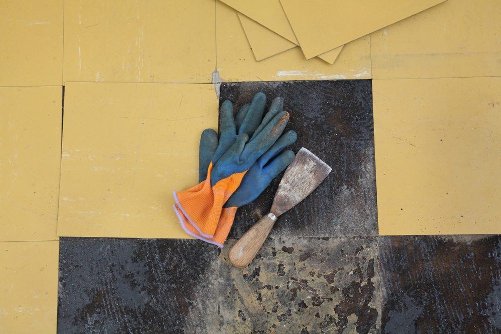 Tools on partially removed vinyl flooring