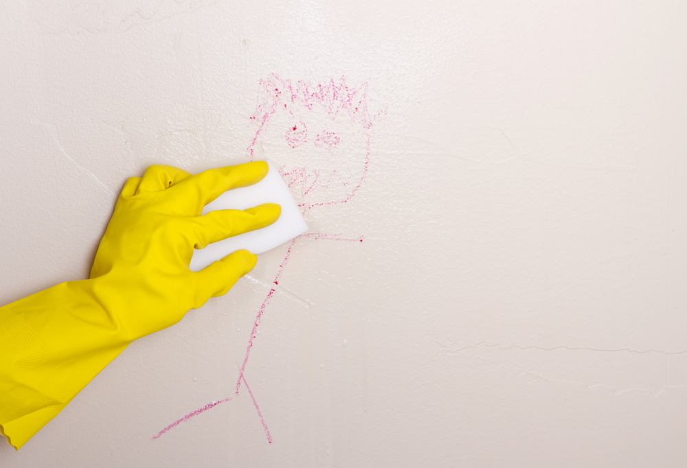 a gloved hand cleans a crayon stick figure off the wall with a sponge