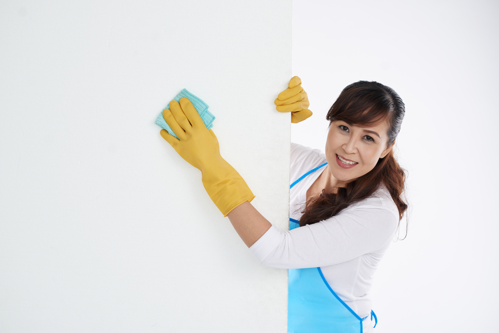 a smiling woman wipes a white wall with a blue cloth